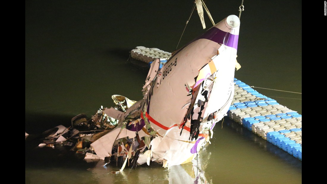 The plane's mangled fuselage gets pulled to the riverbank February 4.