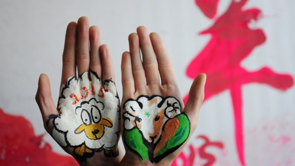 College students in China's Shandong province paint sheep on their hands on Tuesday, December 30.