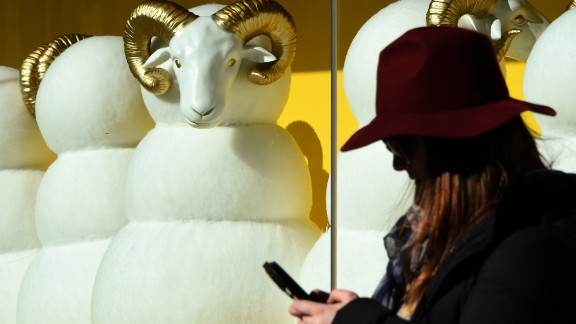 A pedestrian checks her cell phone in front of a department store in Tokyo on Friday, December 26.