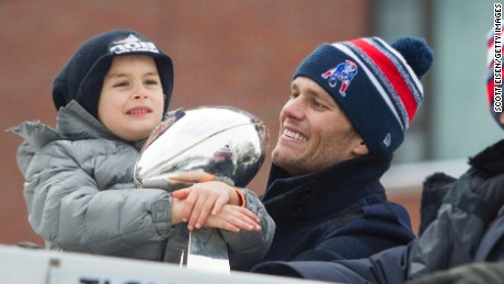 Benjamin Brady, left, holds the Lombardi trophy next to his dad, Patriots quarterback Tom Brady, on a duck boat during the New England Patriots victory parade February 4 in Boston.