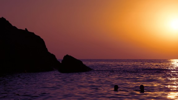 Two swimmers enjoy a sunset over Artemis' Cove.