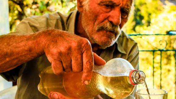 Alexandro Koufadakis, 84, pours a lunchtime glass of homemade wine.