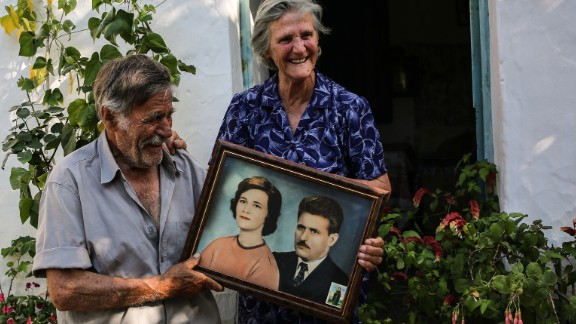 """The term """"Blue Zones"""" has been used to describe small pockets of the world where people, on average, live longer and healthier lives. One such Blue Zone is the Greek island of Ikaria, where octogenarians Alexandro and Antiiopi Koufadakis live. The couple, holding a portrait here of their younger selves, have been married for 61 years."""