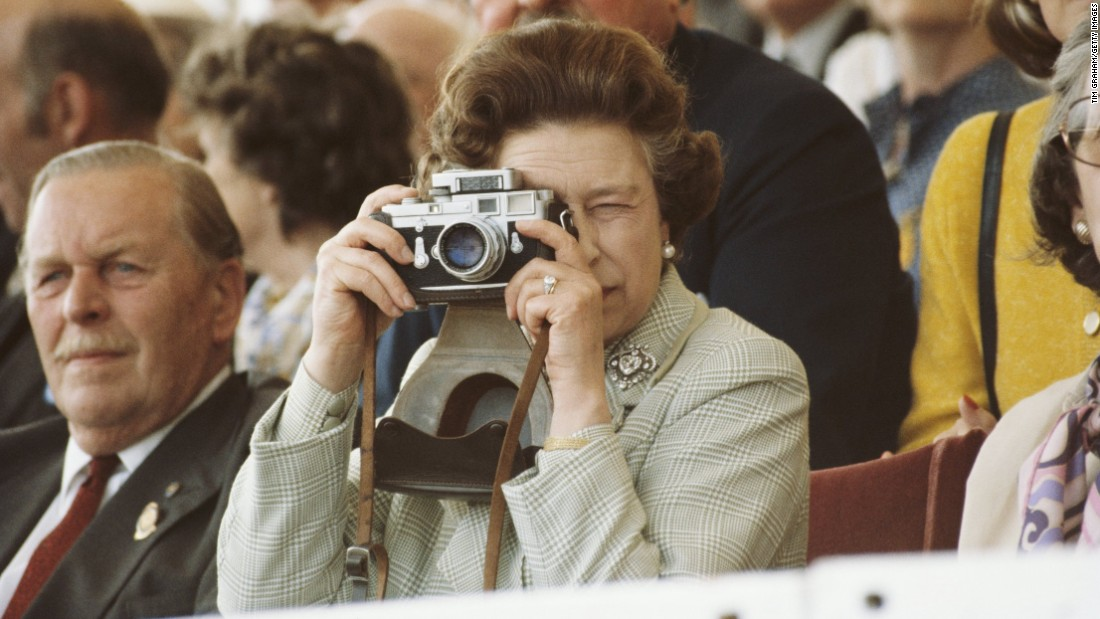 Queen Elizabeth II takes pictures of her husband during a horse show in Windsor, England, on May 16, 1982.