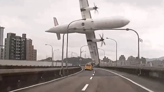 This screen grab taken from video provided courtesy of TVBS Taiwan on February 4, 2015 shows a TransAsia ATR 72-600 turboprop plane clipping an elevated motorway and hitting a taxi (C) before crashing into the Keelung river outside Taiwan's capital Taipei in New Taipei City. The low-flying passenger plane, TransAsia Flight GE235 with 58 people on board, clipped the bridge and plunged into the river outside Taiwan's capital with at least 11 feared dead and many trapped inside.