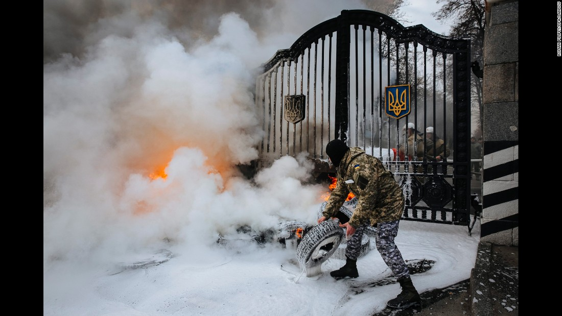 A Ukrainian serviceman with the Aydar volunteer battalion prepares to throw a tire over the gates of the Ukrainian Defense Ministry during a demonstration in Kiev on Monday, February 2. According to local media, Aydar volunteers were protesting against the disbandment of their battalion.