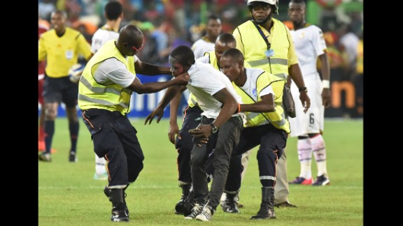 Security officers grab a supporter who got onto the pitch during the African Cup of Nations semifinal between Equatorial Guinea and Ghana on Thursday, February 5.