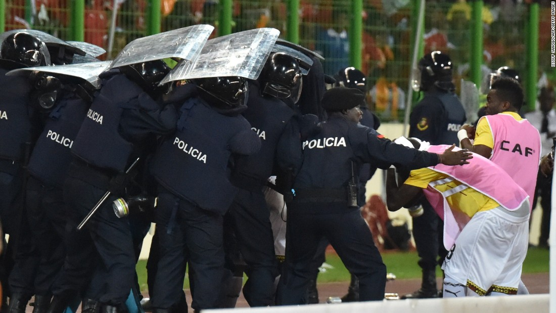 Ghana players leave the pitch protected by riot police at halftime.