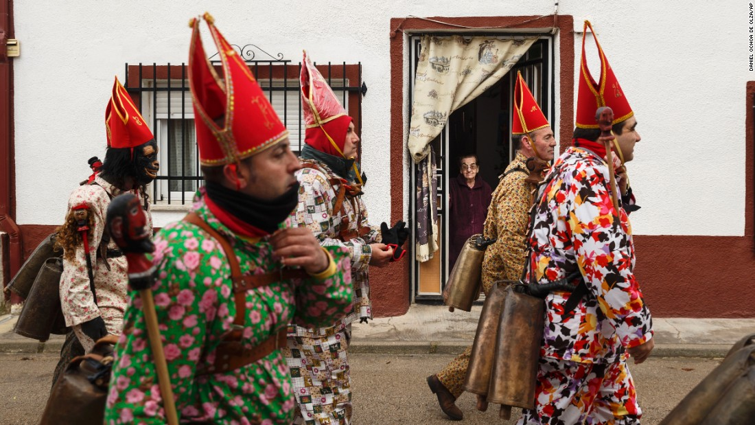 "A woman watches members of the Endiablada brotherhood as they march by her home Tuesday, February 3, during the traditional Endiablada festival in Almonacid Del Marquesado, Spain. During <a href=""http://www.laendiablada.com/history.php"" target=""_blank"">the festival,</a> men from the town dress up as devil-type characters in colorful jumpsuits and red miter hats."