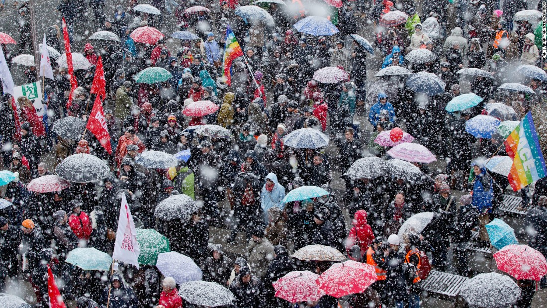 People hold a rally against racism while snow falls Friday, January 30, in Nuremberg, Germany.
