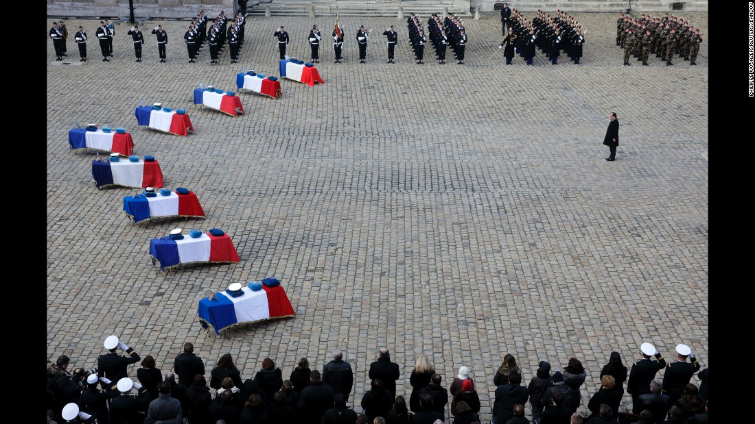 French President Francois Hollande pays his respects Tuesday, February 3, near the flag-draped coffins of nine French Air Force members who died in an accident last month in Albacete, Spain.