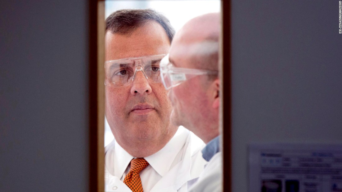 New Jersey Gov. Chris Christie, left, wears safety glasses during his visit to the headquarters of One Nucleus, a life science company in Cambridge, England, on Monday, February 2.