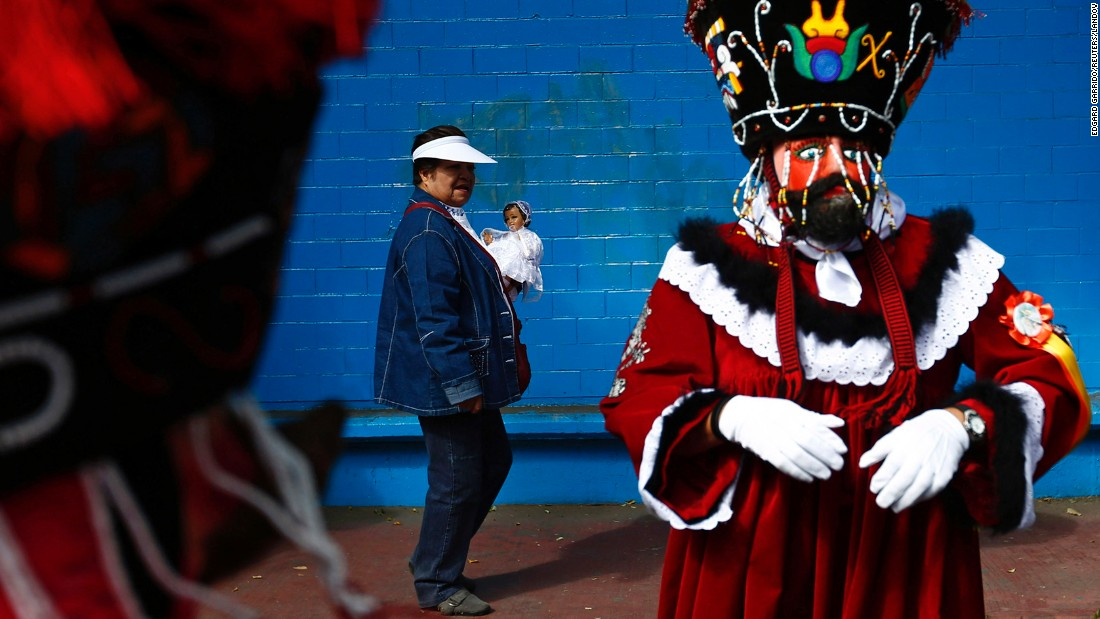 A Chinelo dancer stands in Xochimilco, a borough of Mexico City, as a woman walks past with a dressed-up doll representing baby Jesus on Monday, February 2. This took place during an anniversary celebration marking the 40th day after Jesus' birth.