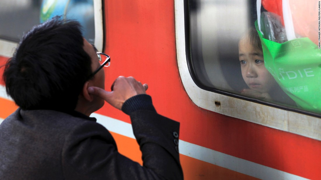 A man gestures to his daughter as she and her mother, not pictured, leave a railway station in Shenzhen, China, on Monday, February 2.