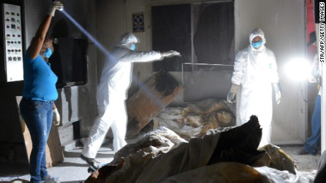 Members of the forensic medical service work at a private crematorium, where corpses in an advanced state of decomposition were found in Acapulco, Guerrero State, on February 6, 2015. Mexican police have found 61 bodies, including children, in an abandoned crematorium that closed more than a year ago in the Pacific resort of Acapulco, authorities said AFP PHOTO (Photo credit should read STR/AFP/Getty Images)