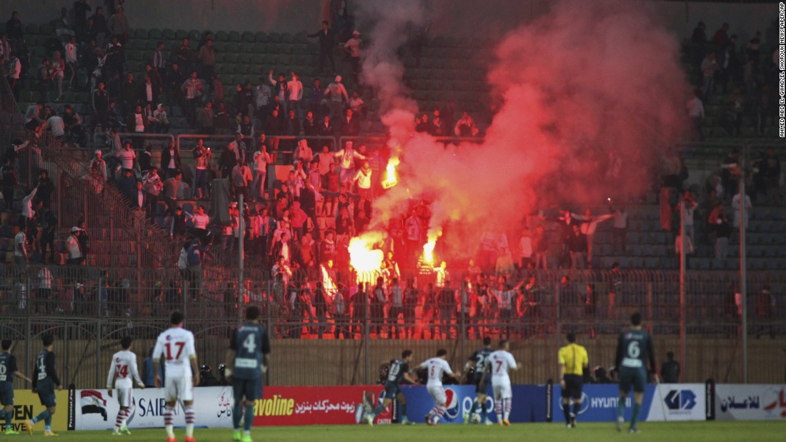 Soccer fans hold flares inside the stadium. The match went ahead despite the violence outside.