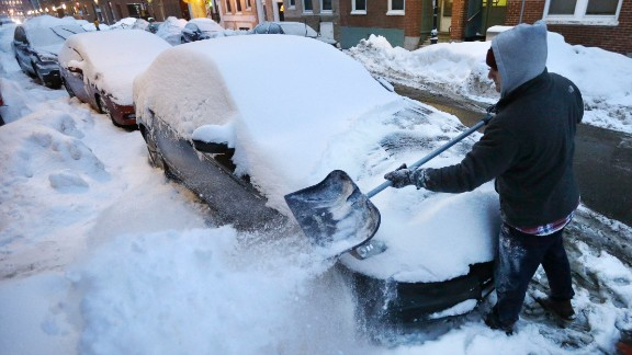 Alex Ranere, of Boston, uses a shovel to remove snow from his car, Sunday, Feb. 8, 2015, in Boston's North End neighborhood. Winter weary New England is being hit with a protracted snowstorm that started Saturday night and could last until early Tuesday morning. (AP Photo/Steven Senne)