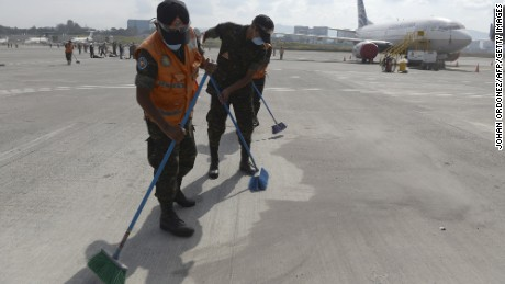 Members of the Guatemalan Army clean ashes off the runway of the closed La Aurora airport in Guatemala on 8 February.