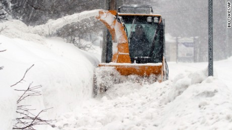 City worker Jeff D'Amico clears snow from a sidewalk, Monday, Feb. 9, 2015, in Marlborough, Mass. New England and portions of New York state awoke Monday to a fresh blanket of snow as a storm threatening to bring up to 1 to 2 feet to some areas churned across the Northeast, making for a slippery, tedious commute to start the workweek. (AP Photo/Bill Sikes)