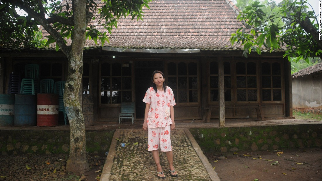 Erwiana stands in front of her family house in Kawis, Indonesia, on April 25 after her successful recovery from months of abuse by her Hong Kong employer.