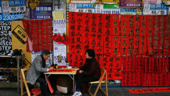 A calligrapher, left, writes auspicious characters on red paper to celebrate the  Lunar New Year in Hong Kong on Wednesday, February 4.