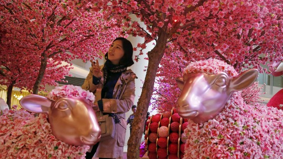 A woman poses for a photograph among decorations in Hong Kong on Friday, February 6.