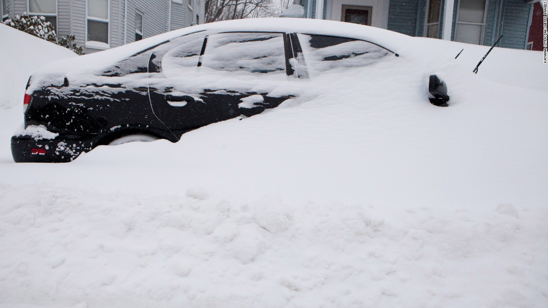 A car is buried in snow in the Dorchester neighborhood of Boston on February 9.