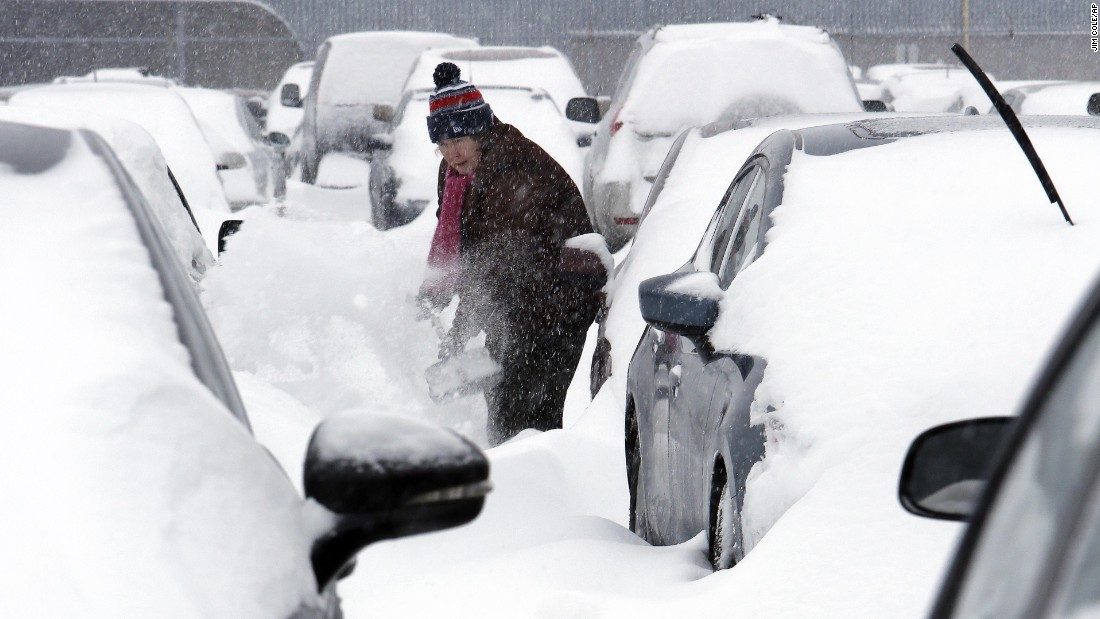 A woman works to dig her car out of the long-term parking lot at the airport in Manchester, New Hampshire, on February 9.