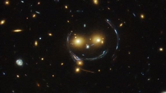 A massive galaxy cluster known as SDSS J1038+4849 looks like a smiley face in an image captured by the Hubble Telescope. The two glowing eyes are actually two distant galaxies. And what of the smile and the round face? That