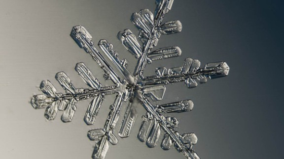 To capture different colors, he uses newspapers, envelopes and other items as a backdrop for the snowflake.