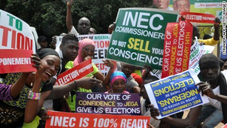 People hold signs to protest postponement of elections, on February 7, 2015 in Abuja. The six-week delay was announced on February 7, 2015 after security chiefs said the military needed more time to secure areas under the control of Boko Haram, the Islamist extremists who have seized swathes of northeastern Nigeria. Presidential and parliamentary elections will now be held on March 28 instead of February 14, said Attahiru Jega, chairman of the Independent National Electoral Commission (INEC). AFP PHOTO / STRINGER (Photo credit should read STRINGER/AFP/Getty Images)