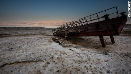 A rusty old dock lying atop a desert encrusted in salt. What used to be the shoreline of the Dead Sea now lies hundreds of feet from the waters edge.