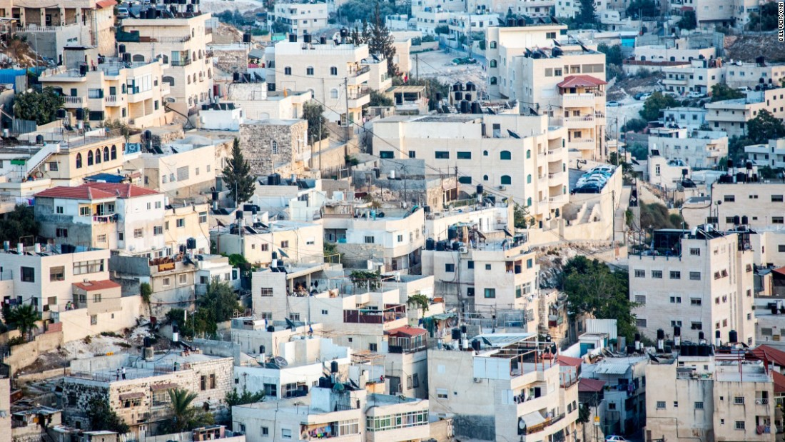 Hundreds of houses and buildings fill a hillside outside the walls of the Old City of Jerusalem.