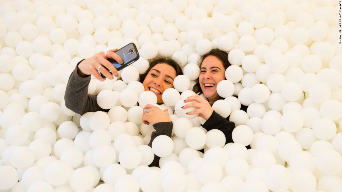 "Visitors of ""Jump In!"" take photos inside the adults-only ball pit Wednesday, February 4, in London. The installation, which holds more than 80,000 white balls, is at the Pearlfisher design agency through February 13."