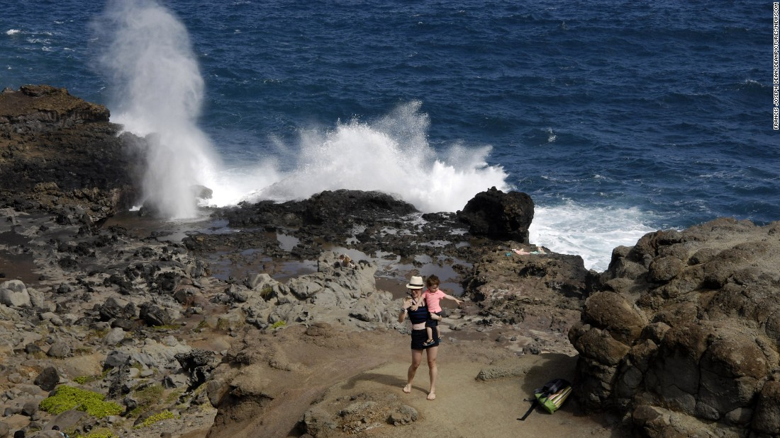 A woman takes a selfie of her and her child while waves crash on the Hawaiian island of Maui on Sunday, February 8.