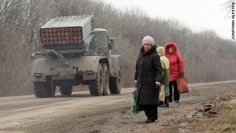Refugees from Debaltseve are escaping the battle zone on foot while Grad missile systems are heading to the front on February 5, 2015, North of Debalteve, Donbass Oblast, Ukraine. Fighting continues between Ukrainian forces and pro-Russian separatists in and around the important rail ray hub of Debalteve. The humanitarian situation in the town has become catastrophic as thousands have fled, while many more are trapped in the heavily shelled town. Locals each day try to flee the battle zone using cars, trucks or buses driven by volunteers making the round trip multiple times a day.