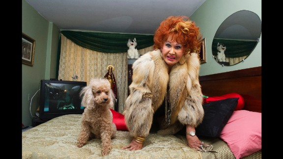 "Sometimes, the women's pets would become ""extras"" in the photographs. Here, Suzette Fontaine strikes a suggestive pose with her dog in New York in 2014."