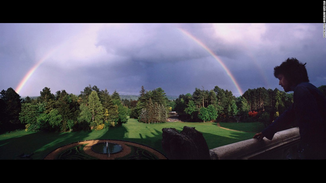 Harrison admires a rainbow from a porch at Friar Park.