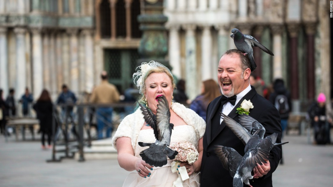 Newlyweds celebrate with the pigeons of St. Mark's Square.