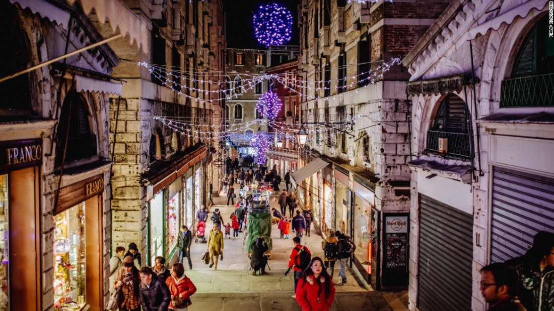 Tourists and holiday shoppers browse the alleyway storefronts near the Rialto Bridge.