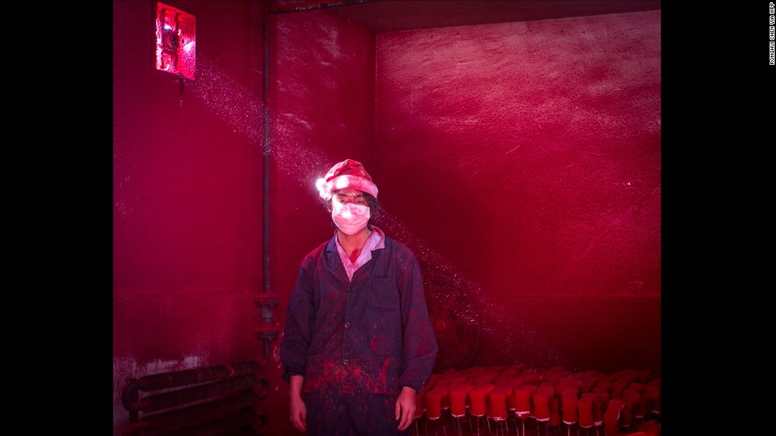 Wei, a 19-year-old Chinese worker, wearing a mask and a Santa hat, stands next to Christmas decorations being dried in a factory in Yiwu, China, as red powder used for coloring hovers in the air. He wears six masks a day and the hat protects his hair from the red dust, which covers workers from head to toe like soot after several hours of work.