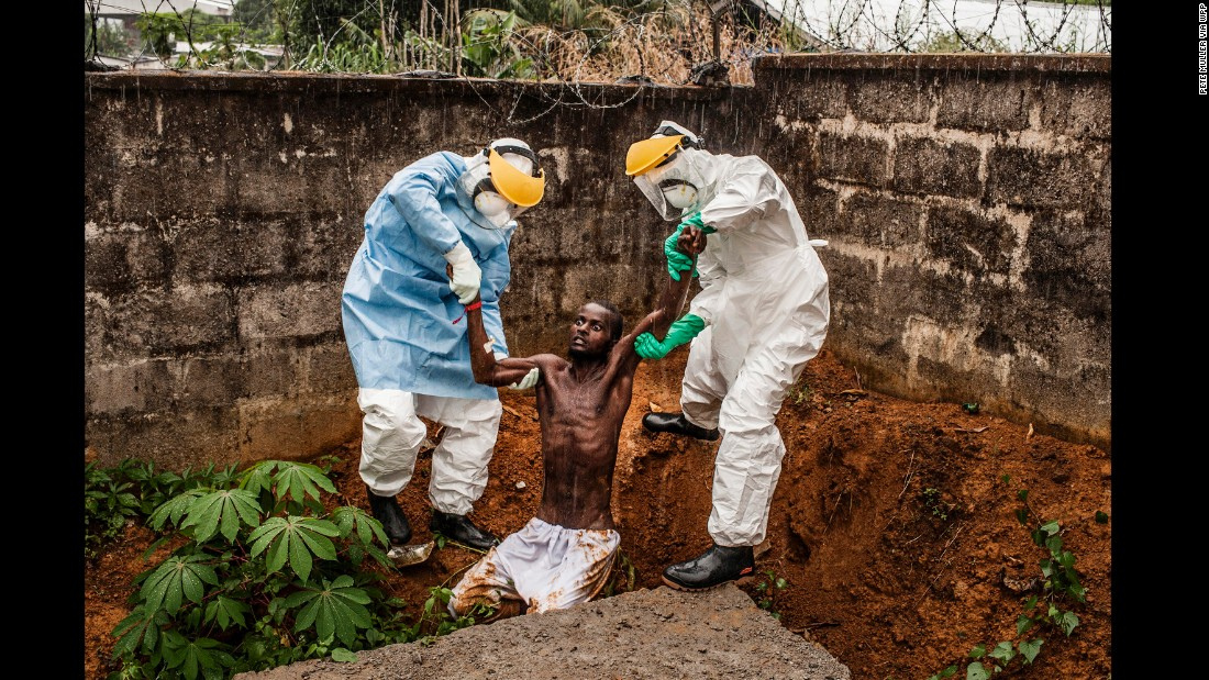 Medical staff at the Hastings Ebola Treatment Center in Freetown, Sierra Leone, work to escort a man in the throes of Ebola-induced delirium back into the isolation ward from which he escaped. The man died shortly after this picture was taken.