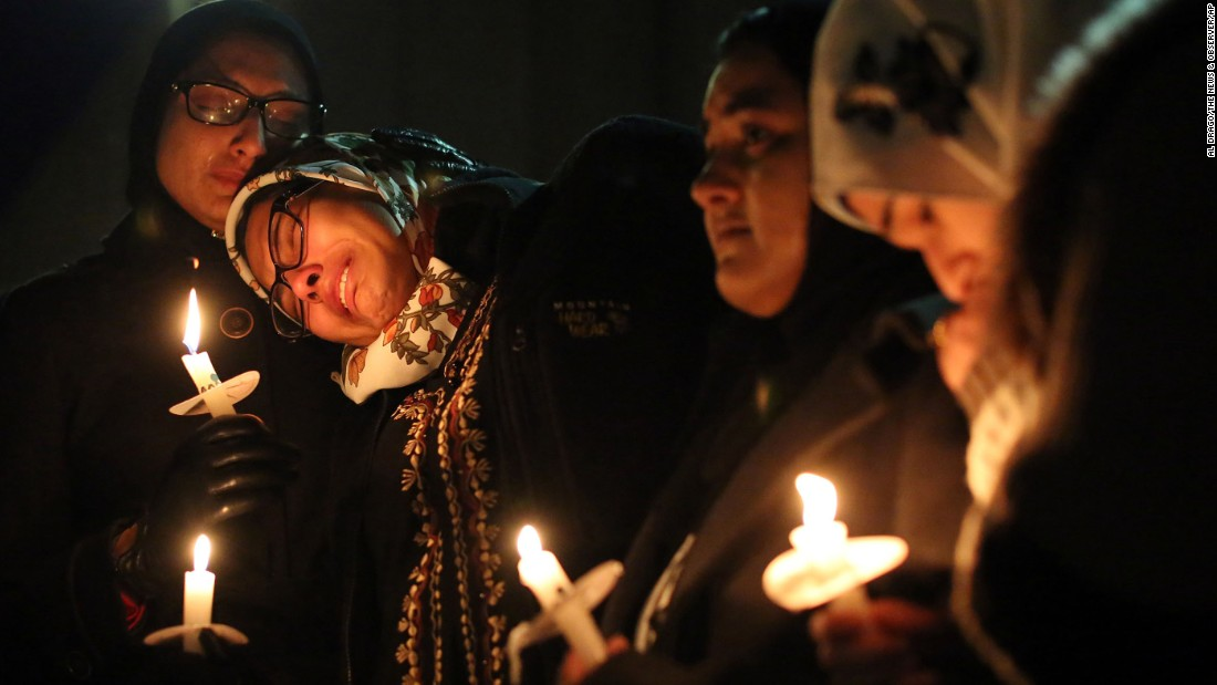 Nida Allam, a senior at North Carolina State University, rests her head on Asheen Allam during a vigil in Chapel Hill on February 11.