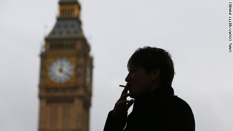 A woman poses for a photograph as she smokes a cigarette on October 15, 2014, in Parliament Square in London, England.