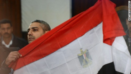 Al-Jazeera journalist Egyptian-Canadian Mohamed Fahmy holds the Egyptian flag at the court in Cairo February 12, 2015. An Egyptian court ordered the release of two Al-Jazeera journalists pending their retrial for allegedly supporting the banned Muslim Brotherhood. Fahmy was ordered to pay bail of 250,000 Egyptian pounds ($33,000) while Egyptian Baher Mohamed was released on his own recognisance along with other defendants. AFP PHOTO/ MOHAMED EL-SHAHEDMOHAMED EL-SHAHED/AFP/Getty Images