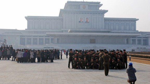 A foreign photographer (kneeling in foreground) takes an officially forbidden photo of soldiers at ease in front of the Kumsusan Palace of the Sun, where Kim Jong Il and his father, Kim Il Sung, lie in a mausoleum.