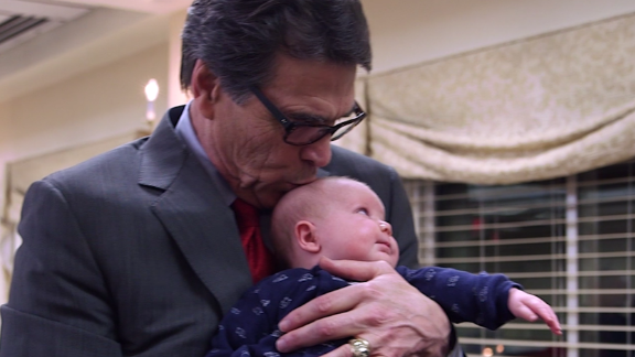 Rick Perry kisses a baby during a visit to New Hampshire on February 11.