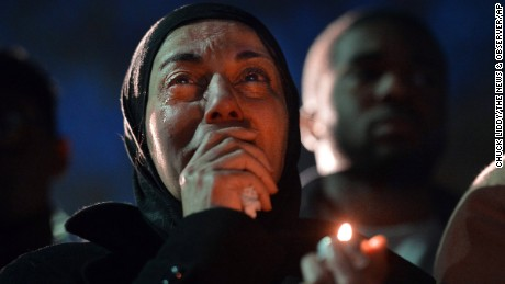 A woman cries during a vigil as she watches photos projected on a screen of three people who were killed at a condominium near UNC-Chapel Hill, Wednesday, Feb. 11, 2015, in Chapel Hill, N.C. Craig Stephen Hicks appeared in court Wednesday on charges of first-degree murder in the deaths Tuesday of Deah Shaddy Barakat, his wife Yusor Mohammad and her sister Razan Mohammad Abu-Salha.