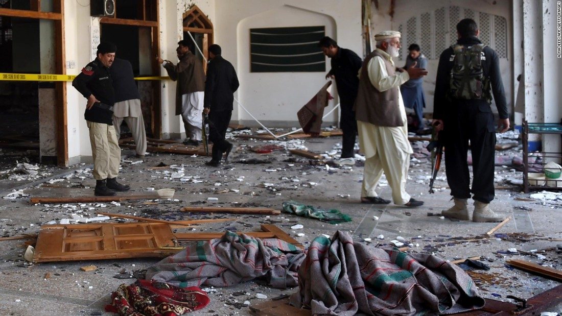 Security personnel inspect the Shiite Muslim mosque after the attack on February 13. Up to five attackers executed the assault, including a suicide bomber and a shooter inside the mosque, Peshawar's police inspector general says.