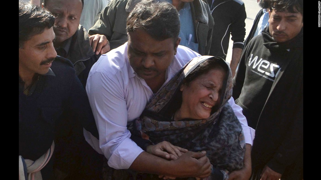 People comfort a woman who lost a relative in the February 13 attack.